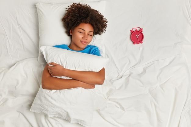 Молодая брюнетка женщина, лежа в постели