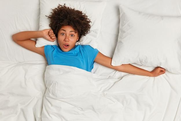 ベッドに横たわっている若いブルネットの女性