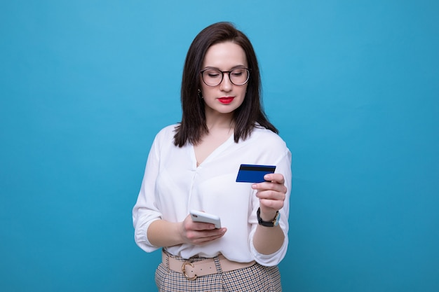 A young brunette woman makes an order online using her phone and bank card