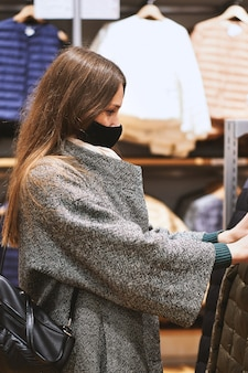 Young brunette woman in medical mask chooses clothes in the store and makes purchases