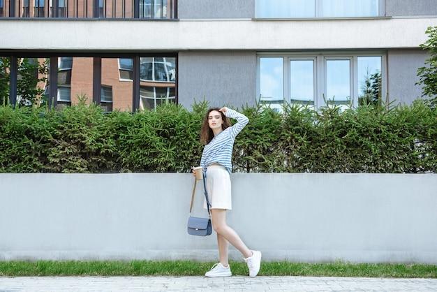 젊은 갈색 머리 여성 모델은 새로운 옷 컬렉션을 입고 도시 거리의 배경에 포즈를 취하고 카메라를 보고 있습니다.