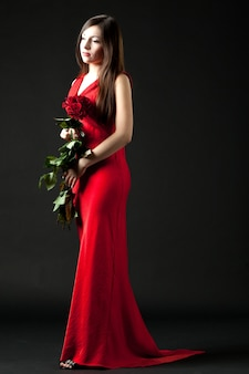 Young brunette woman model in red long evening dress standing and holding bouquet of red roses in hands over dark background in photo studio