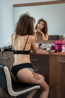 Young brunette woman in the morning sits in her bedroom in front of the mirror just woke up