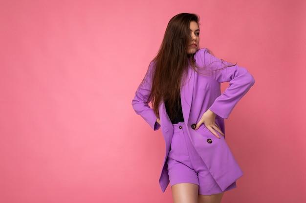 Молодая брюнетка женщина красивый привлекательный очаровательный элегантный модный серьезный изолированный на розовом цветном фоне с пустым пространством для текста