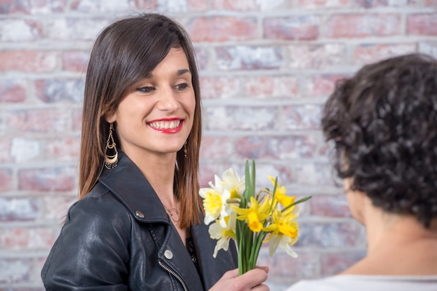 Young brunette woman offers bouquet of daffodils