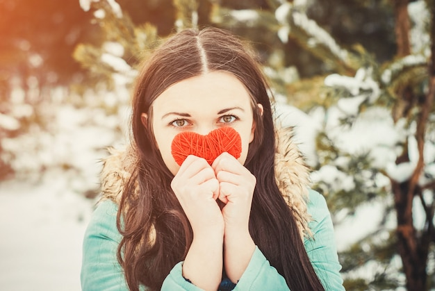 Young brunette woman outdoor holding red knitted heart