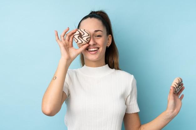 Молодая брюнетка женщина над синей стеной, держа пончик и счастливым