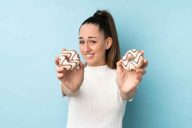 Молодая брюнетка женщина над синей стеной, держа пончик и грустно
