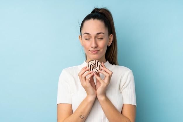 Молодая брюнетка женщина над синей стеной, держа пончик