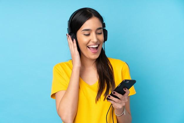 Молодая женщина брюнет над изолированной музыкой голубой стены слушая с чернью и пением