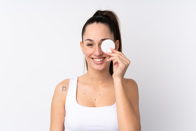 그녀의 얼굴에서 화장을 제거하고 웃는 면화 패드와 격리 된 흰 벽에 젊은 갈색 머리 여자