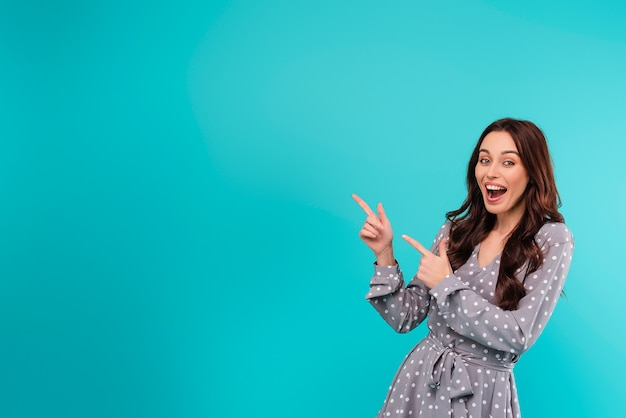 Young brunette woman pointing at copyspace on the left isolated over turquoise blue background