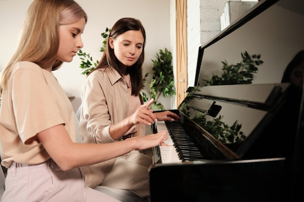 Young brunette woman pointing at piano key while consulting and teaching her teenage daughter or student during home lesson