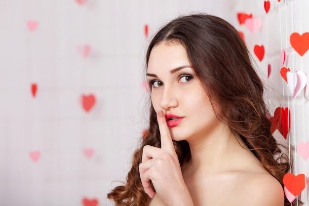 彼の口に指を保持している若いブルネットの女性の肖像画