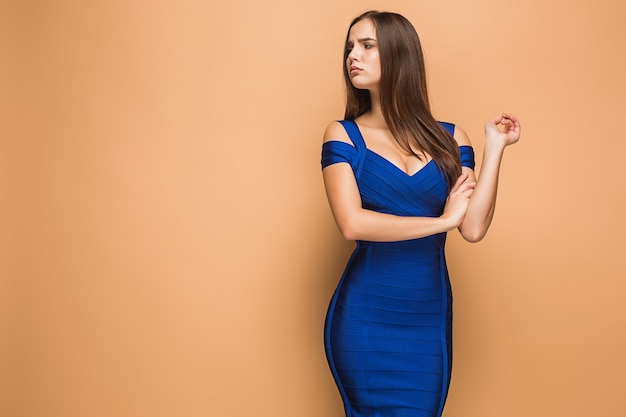 茶色の背景に青いドレスでポーズをとって若いブルネットの女性