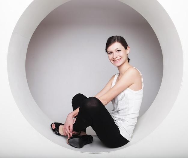 円でポーズをとる若いブルネットの女性