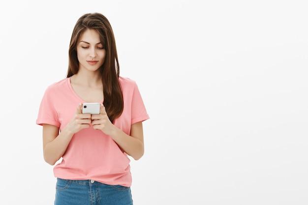 Молодая брюнетка женщина позирует в студии со своим телефоном