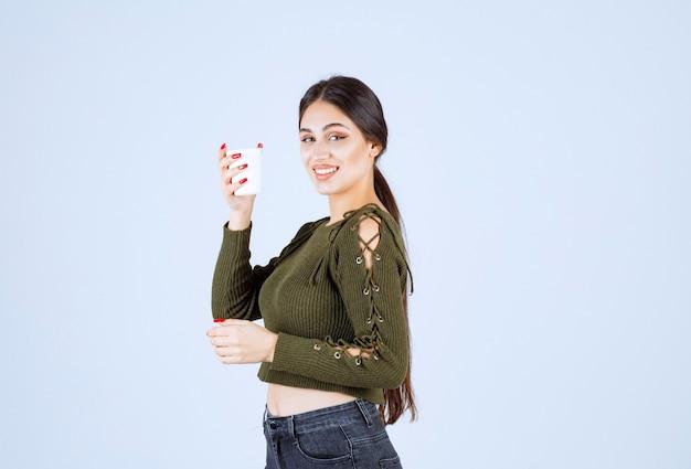 흰색 바탕에 행복 하 게 플라스틱 컵 포즈 젊은 갈색 머리 여자.
