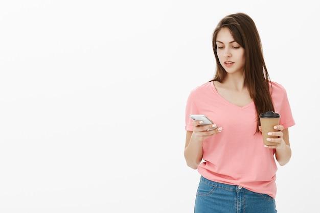 Giovane donna castana in posa in studio con il suo telefono e caffè