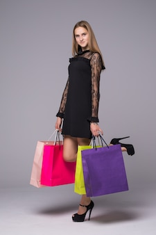 Young brunette woman posing with shopping bags and looking at camera