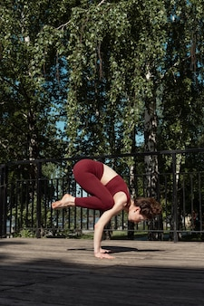 Young brunette woman practicing bakasana crow pose in the park on wooden platform