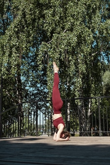 Young brunette woman practicing salamba sirsasana headstand pose in the park on wooden platform