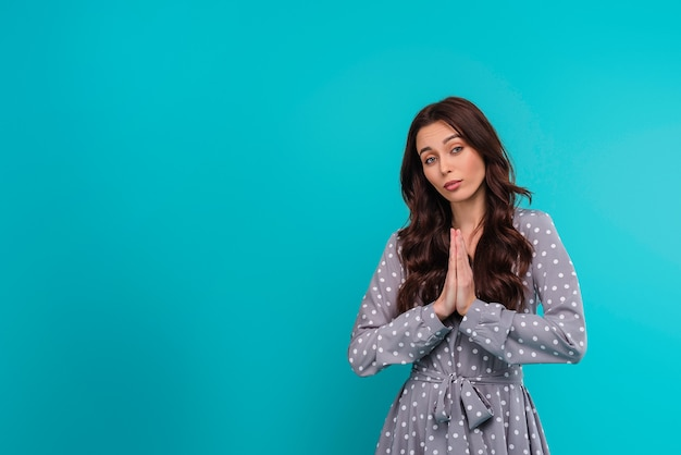 Young brunette woman praying isolated