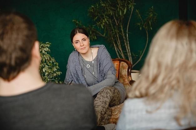 젊은 브루네트 여성 심리학자는 약속 시간에 결혼한 부부의 맞은편에 앉는다
