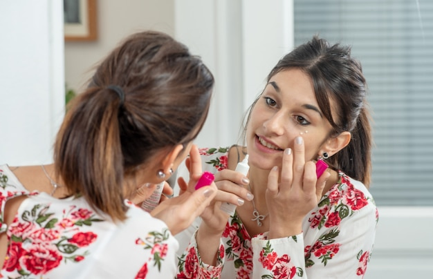 Young brunette woman putting makeup in the mirror