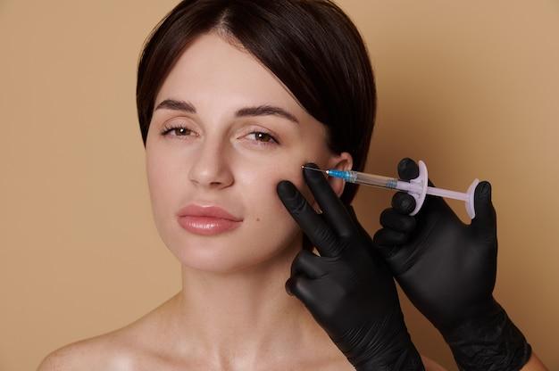 노화 방지 치료를 받는 젊은 갈색 머리 여자. 여성의 얼굴에 히알루론산 주사를 만드는 의료용 장갑을 끼고 있습니다. 주사 미용 및 성형 수술 개념, 복사 공간