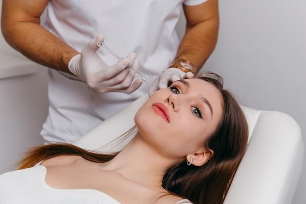 그녀의 얼굴 근접 촬영 초상화에 성형 수술 주입을받는 젊은 갈색 머리 여자