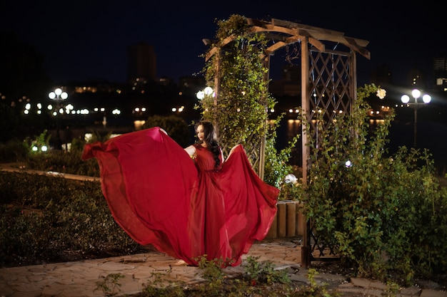 Young brunette woman in a red dress with a train posing in a night park