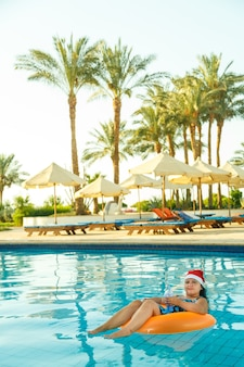 Young brunette woman in santa claus hat in a swimming circle in the pool in the christmas holidays on the background of palm trees.
