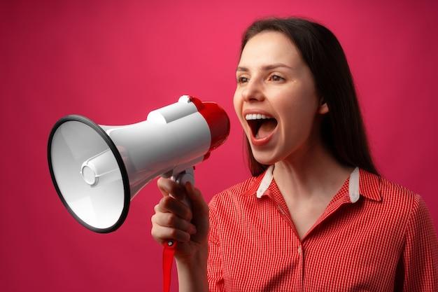 ピンクの背景にメガホンで叫んでいる若いブルネットの女性