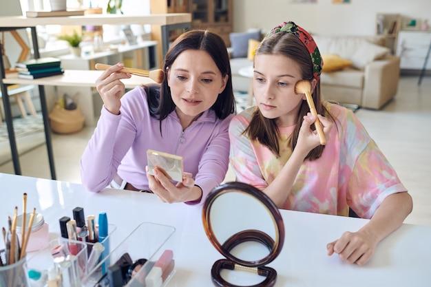 귀여운 10대 딸이 집에서 거울을 보면서 얼굴에 가루를 바르거나 얼굴을 붉히는 방법을 보여주는 젊은 브루네트 여성 프리미엄 사진