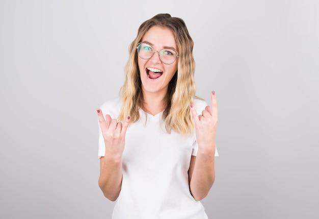 Молодая брюнетка женщина показывает жест рукой рок-н-ролл позирует в студии.