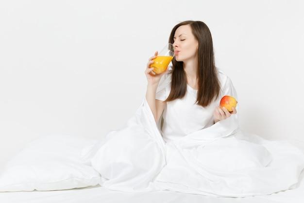 젊은 갈색 머리 여자는 흰색 시트, 베개, 흰색 벽에 격리된 담요에 싸여 침대에 앉아