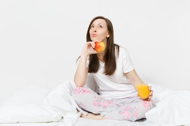 Молодая брюнетка женщина сидит на кровати с белой простыней, подушкой, завернувшись в одеяло, изолированное на белой стене