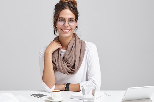 机に座っている若いブルネットの女性