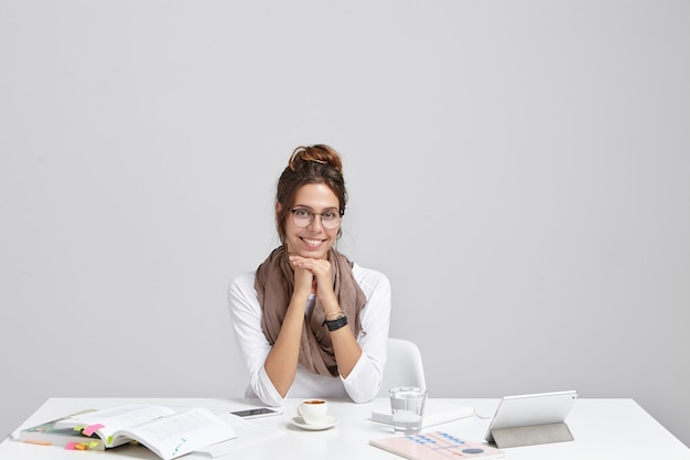 Молодая брюнетка женщина, сидящая за столом