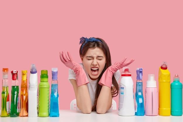 Giovane donna bruna seduta accanto a prodotti per la pulizia