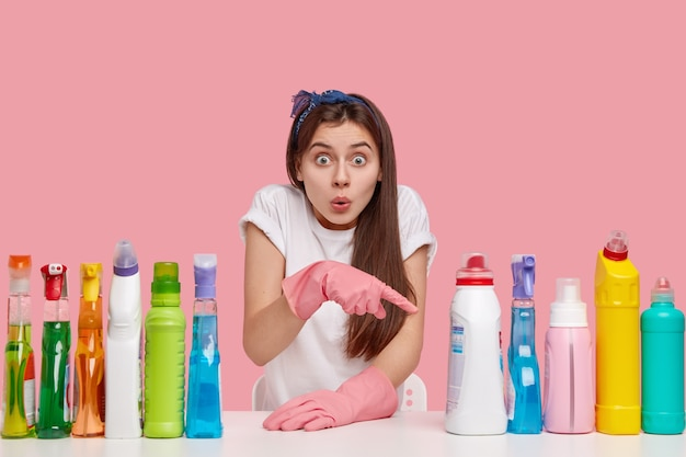 Young brunette woman sitting next to cleaning products