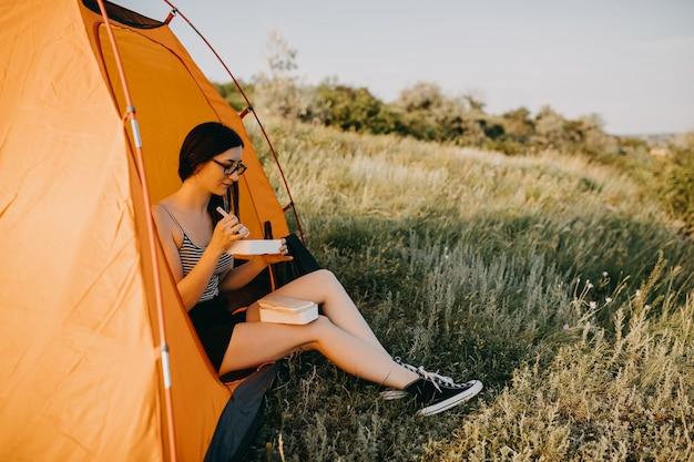 ランチボックスから食べて、テントの中に座っている若いブルネットの女性。