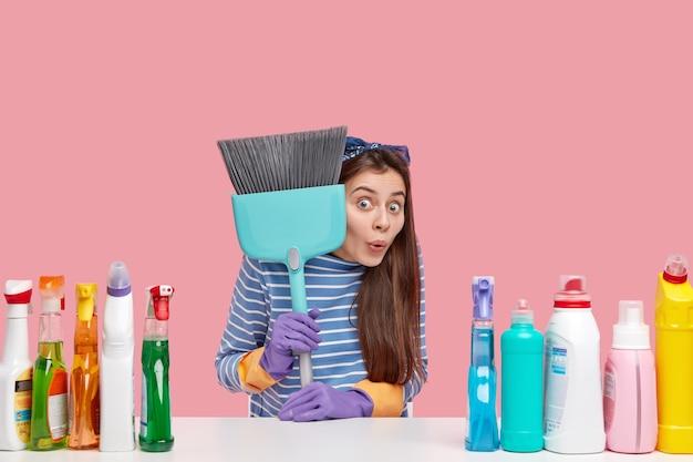Молодая брюнетка женщина сидит рядом с чистящими средствами