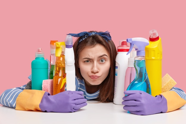 クリーニング製品の隣に座っている若いブルネットの女性
