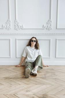 젊은 갈색 머리 여성이 바닥에 앉아서 새로운 의류 카탈로그 컬렉션에서 스튜디오에서 포즈를 취했습니다.