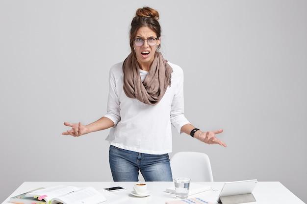 Молодая брюнетка женщина, стоящая возле стола