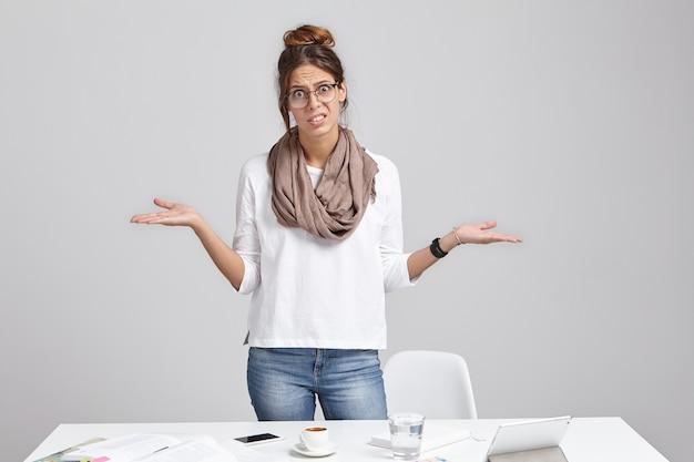 机の近くに立っている若いブルネットの女性