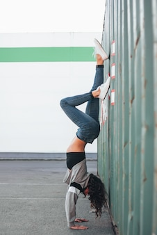 Young brunette woman street dancer gymnast standing on her arms