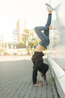 그녀의 팔에 서있는 젊은 갈색 머리 여자 거리 댄서 체조
